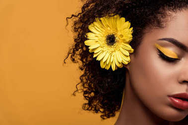 Close-up portrait of young sensual african american woman with artistic make-up and gerbera in hair isolated on orange background
