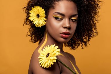 Young bright african american woman with artistic make-up and gerbera in hair looking away isolated on orange background