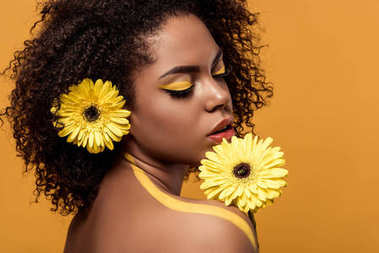 Attractive young american woman with artistic make-up smelling gerbera isolated on orange background