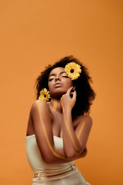 Young tender african american woman with artistic make-up and gerbera in hair isolated on orange background