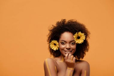 Young smiling african american woman with artistic make-up and gerbera in hair isolated on orange background
