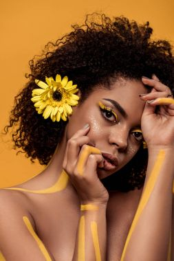 Beautiful african american woman with artistic make-up and gerbera in hair with hands near face isolated on orange background