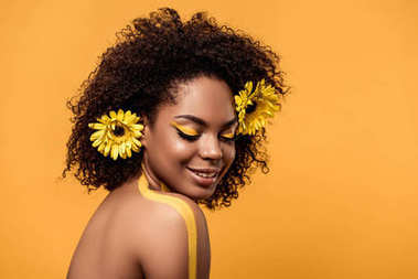 Young sensual african american woman with artistic make-up and gerberas in hair isolated on orange background