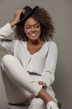 Beautiful african american woman in white clothes smiling and holding black hat isolated on grey background