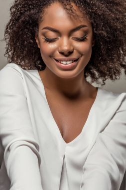 Stylish african american woman in white shirt smiling and looking down isolated on grey background