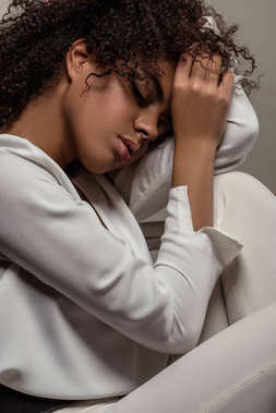 Young sensual african american woman in white shirt dreaming isolated on grey background