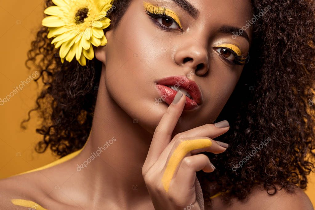 Young sensual african american woman with artistic make-up and gerbera in hair with finger on lips isolated on orange background