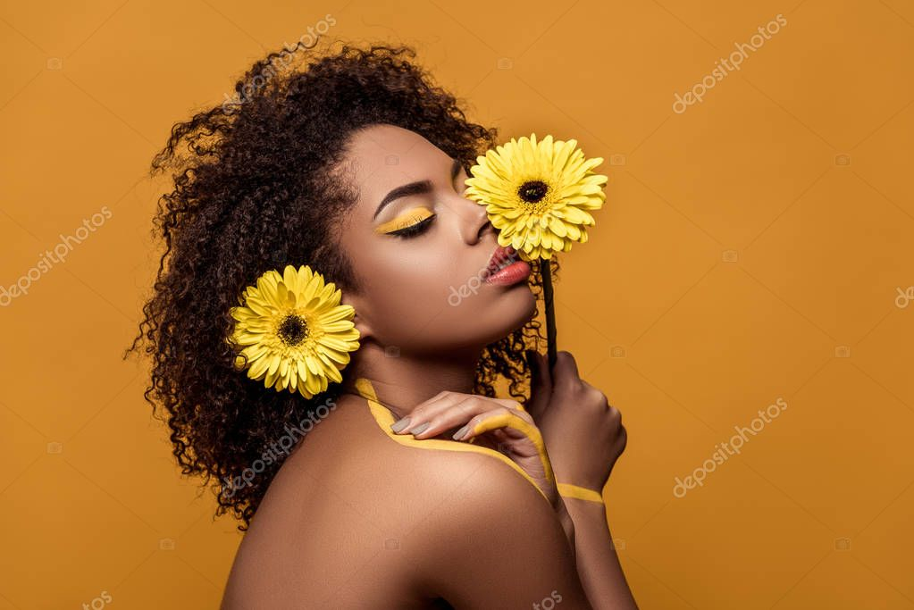 Stylish african american woman with artistic make-up holds flower by her face tenderly touches her skin isolated on orange background