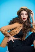 gyönyörű fiatal nő, elegáns canotier kalapot és kabátot keres el