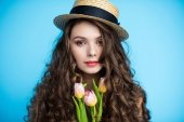 attractive young woman with long curly hair in canotier hat holding beautiful tulips