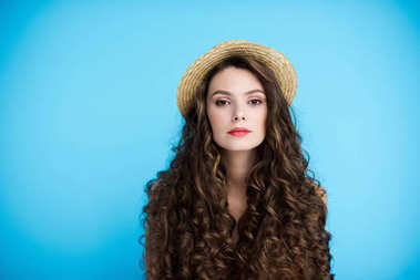 beautiful young woman in canotier hat on long curly hair isolated on blue