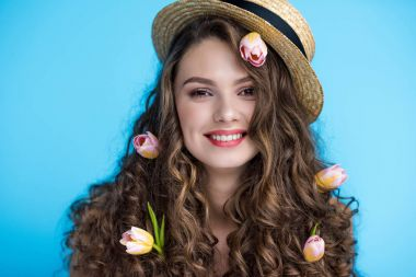 happy young woman in canotier hat with flowers in her long curly hair