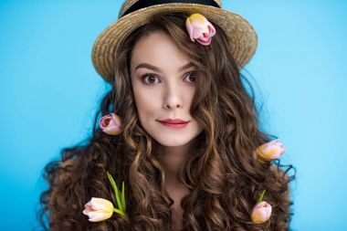 playful young woman in canotier hat with flowers in her long curly hair looking at camera