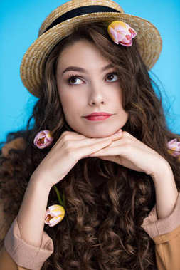 thoughtful young woman in canotier hat with flowers in her long curly hair