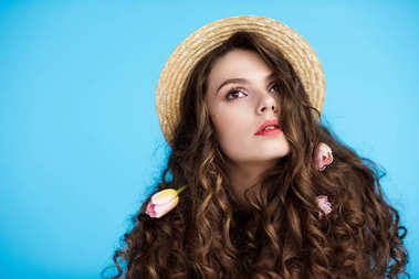 attractive young woman in canotier hat with flowers in her long curly hair isolated on blue