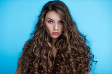 attractive young woman with long curly hair isolated on blue