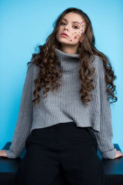 attratcive young woman with flowers on face in stylish sweater sitting on table