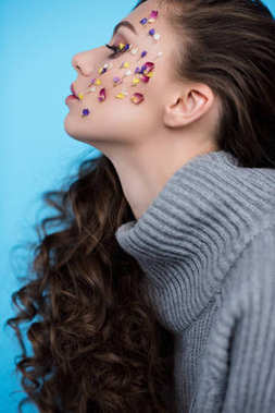 side view of young woman with flowers on face in warm sweater isolated on blue