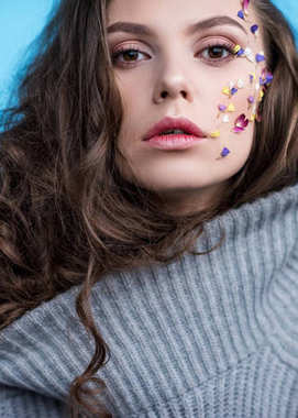 close-up portrait of woman in warm grey sweater with flowers attached to face