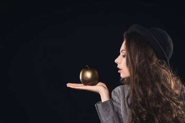 side view of fashionable young woman holding golden apple on palm isolated on black