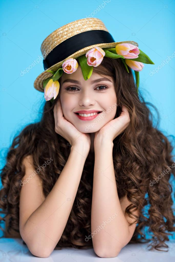 smiling young woman in canotier hat with fresh tulips under it