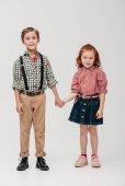 Fotografie entzückende kleine Kinder, die sich an den Händen halten und vereinzelt in die Kamera lächeln