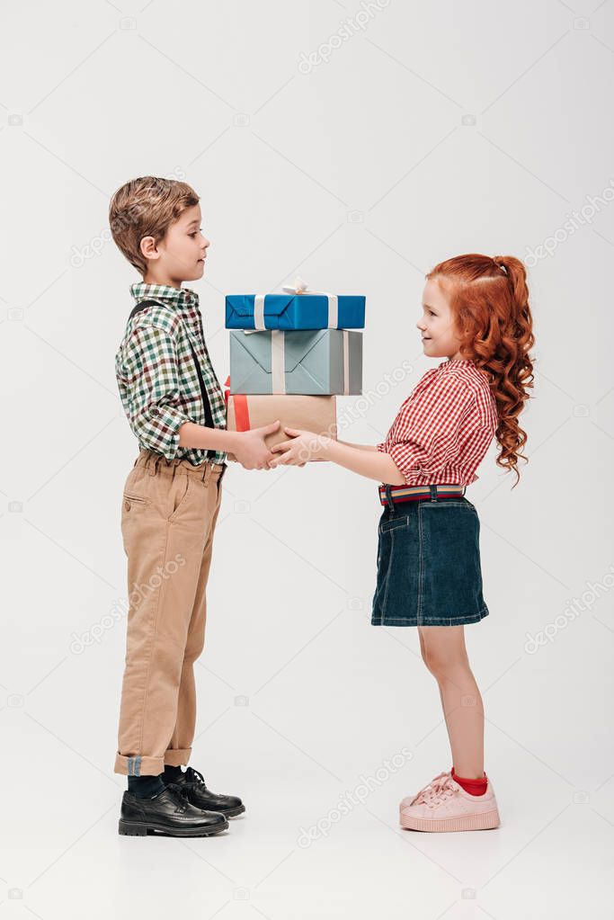 side view of adorable happy kids holding presents isolated on grey