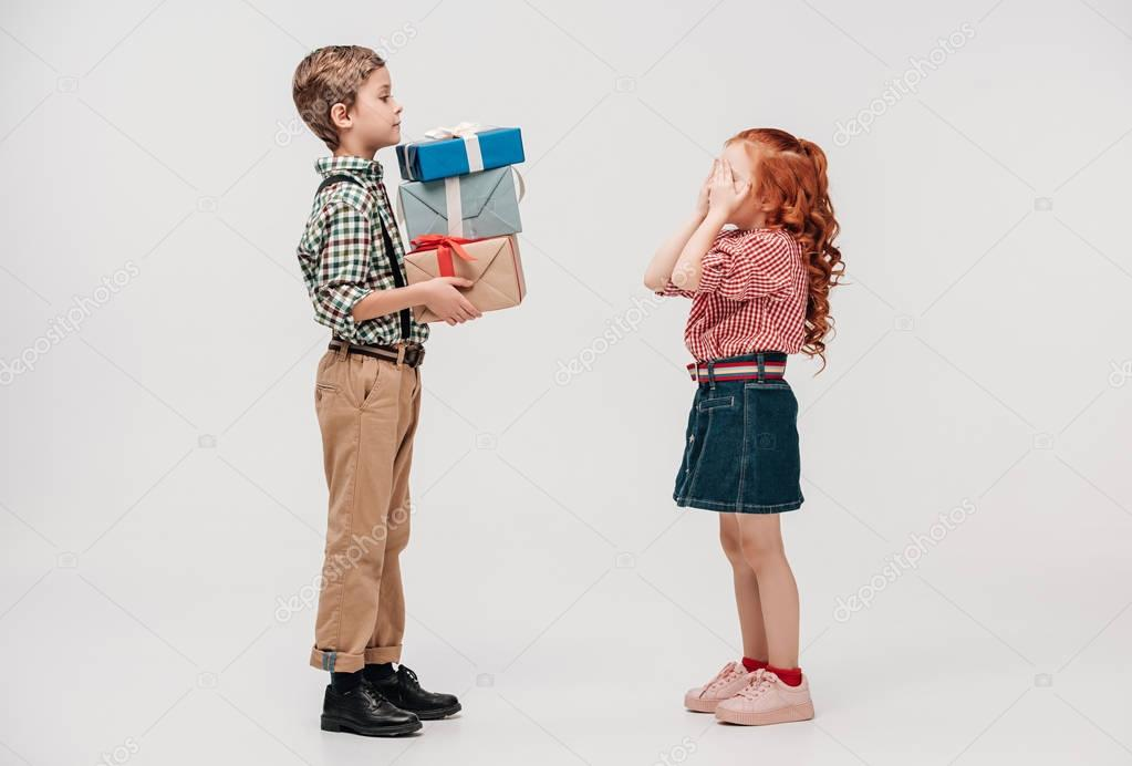 side view of boy presenting gifts to cute little girl closing eyes isolated on grey