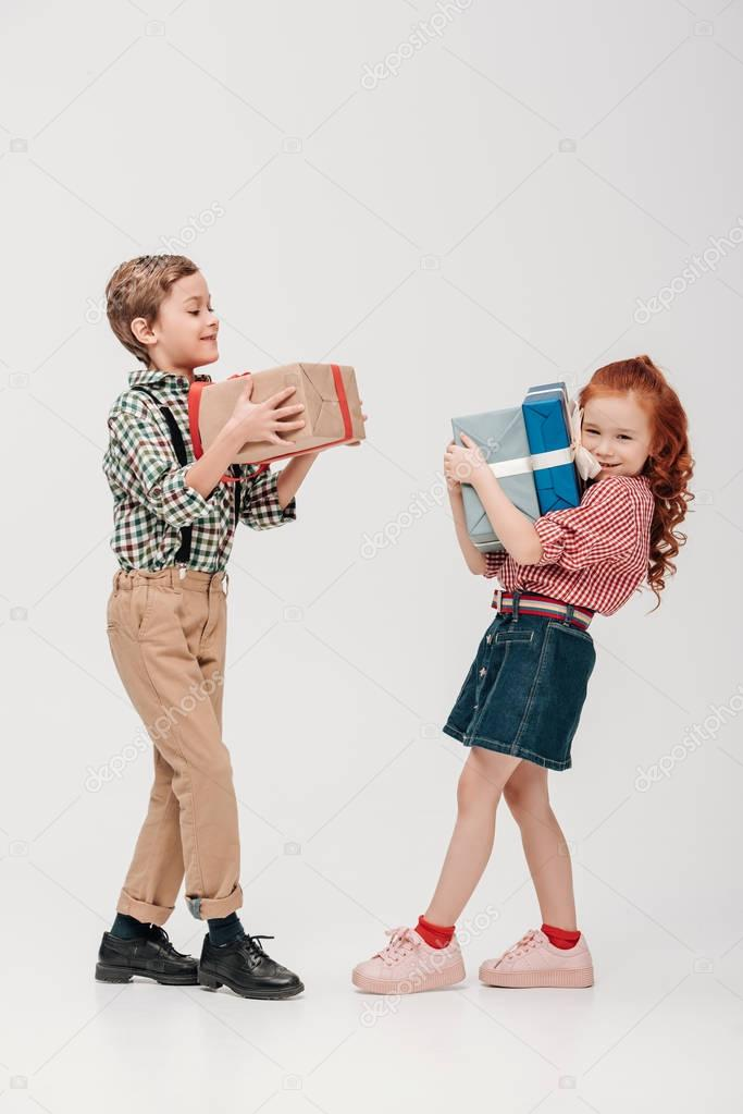 adorable little kids holding colorful gift boxes isolated on grey
