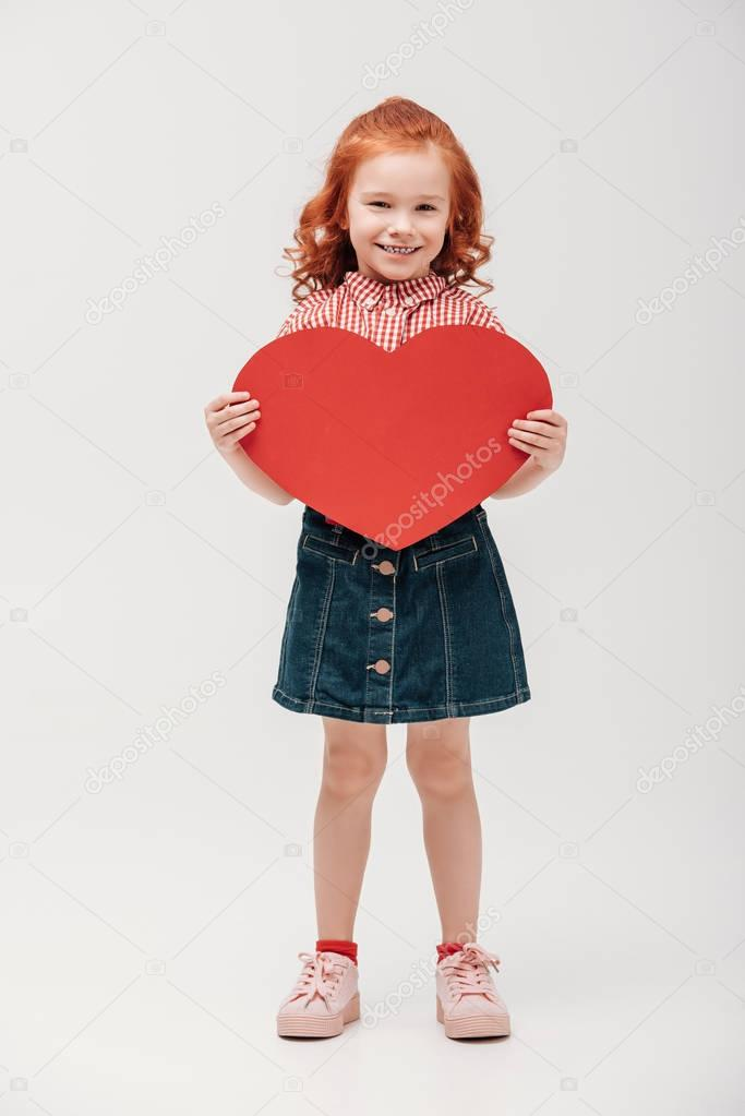 beautiful little child holding red heart symbol and smiling at camera isolated on grey