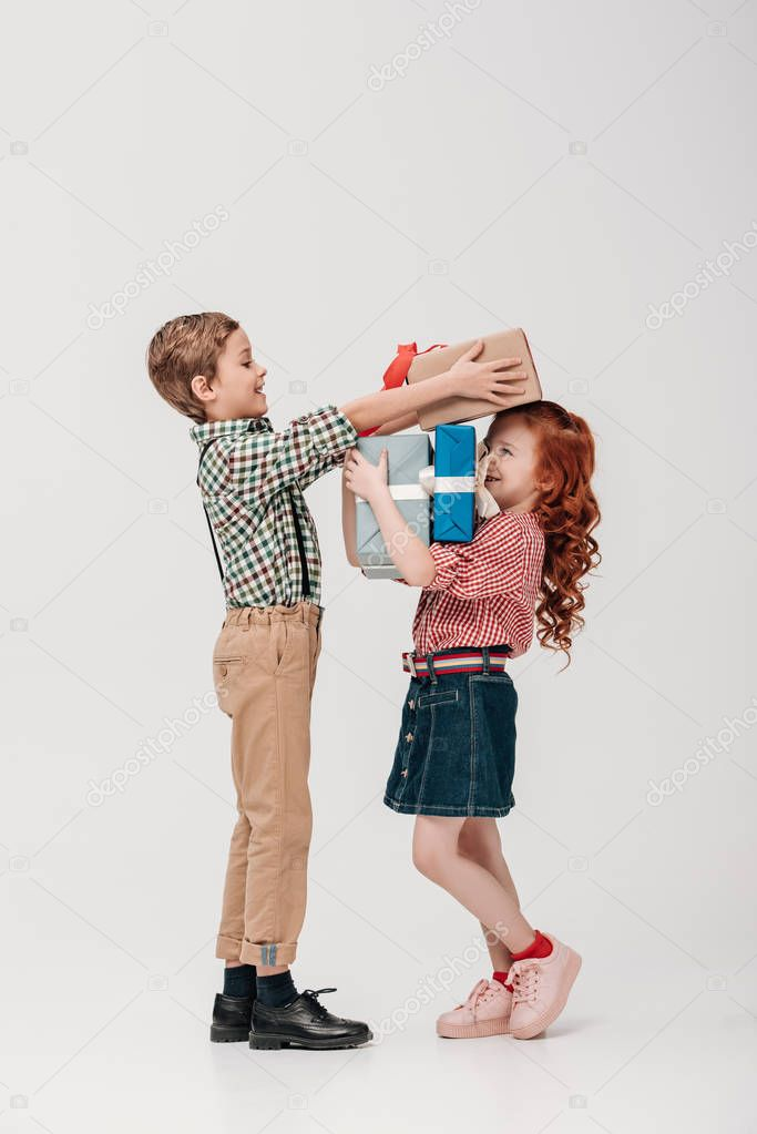 side view of happy boy presenting gift boxes to smiling little girl isolated on grey