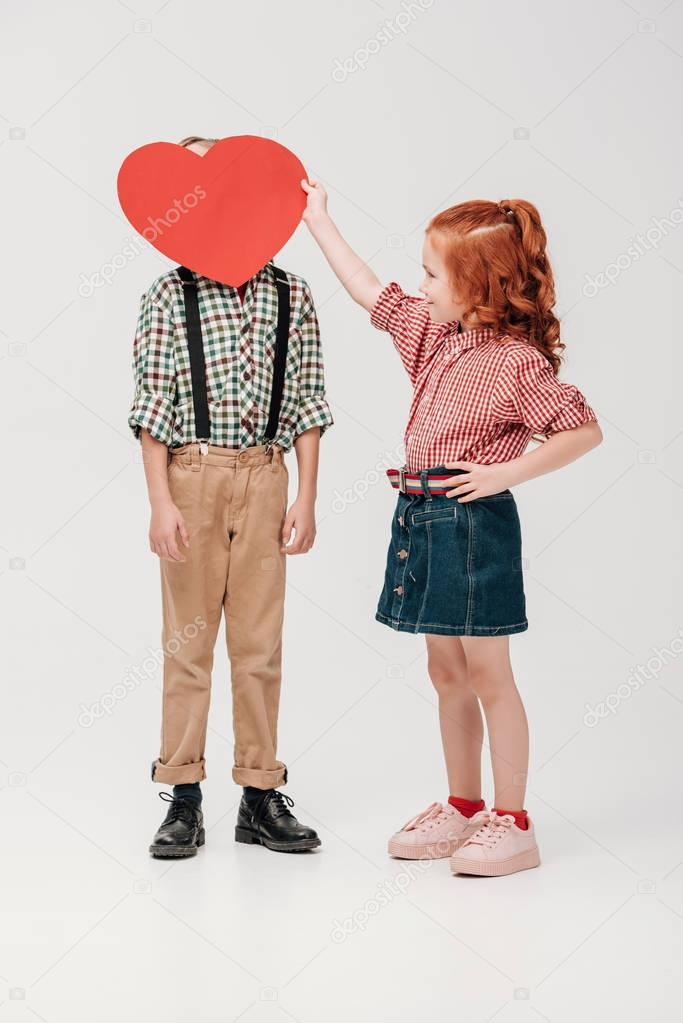 little girl holding red heart symbol near face of little boy isolated on grey
