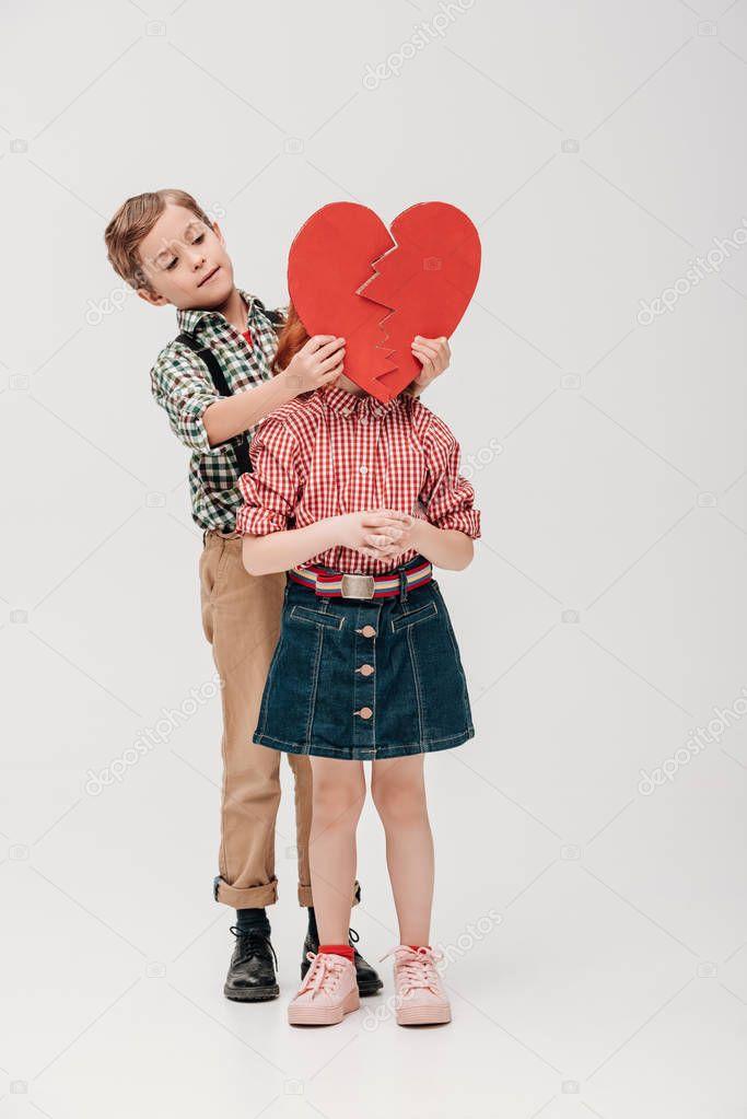 little boy holding broken heart symbol near face of little girl isolated on grey
