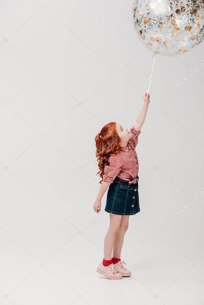 adorable redhead child holding big round shiny balloon isolated on grey