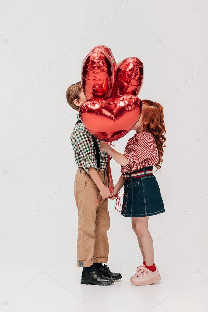 side view of beautiful little couple standing with heart shaped balloons isolated on grey