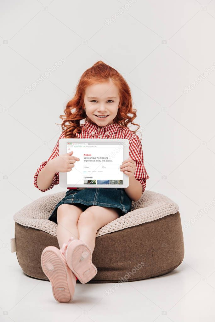 adorable little girl smiling at camera while holding digital tablet with airbnb website on screen isolated on grey