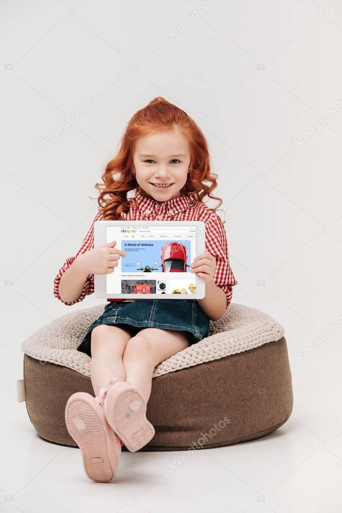 adorable little girl smiling at camera while holding digital tablet with ebay website on screen isolated on grey