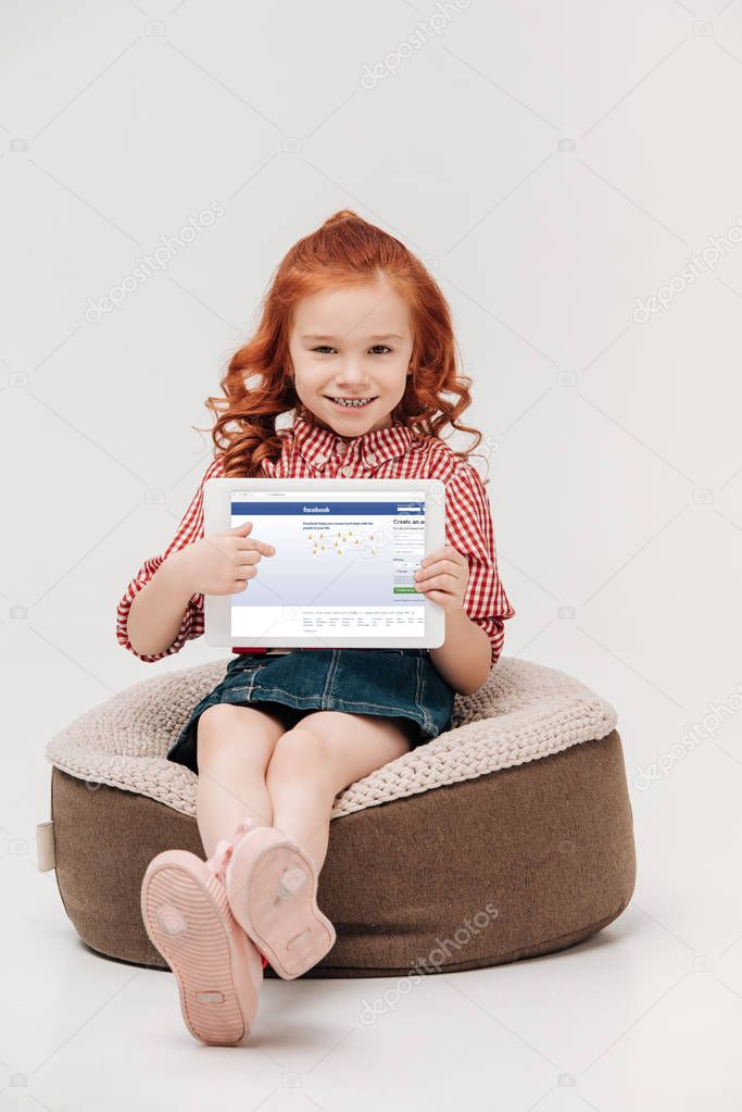 adorable little girl smiling at camera while holding digital tablet with facebook website on screen isolated on grey