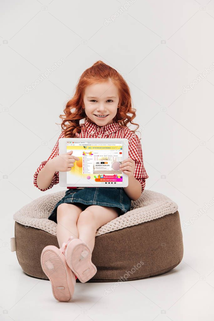 adorable little girl smiling at camera while holding digital tablet with aliexpress website on screen isolated on grey