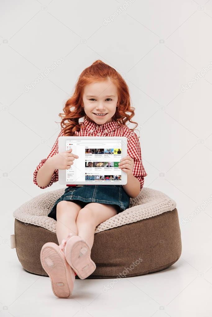 adorable little girl smiling at camera while holding digital tablet with youtube website on screen isolated on grey