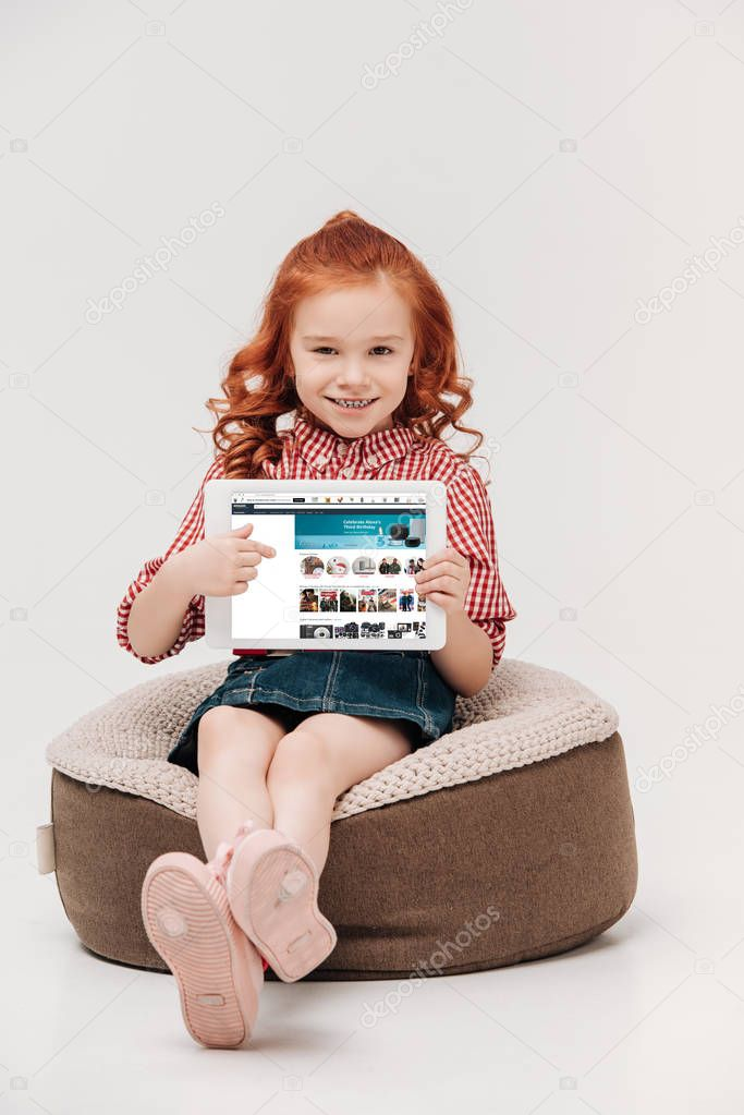 adorable little girl smiling at camera while holding digital tablet with amazon website on screen isolated on grey