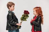 Fotografie boční pohled na malého chlapce prezentovat Kytice růží se svou přítelkyní izolované Grey