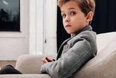 Fotografie Stylový malý chlapec sedí v pohodlném křesle a pomocí smartphonu