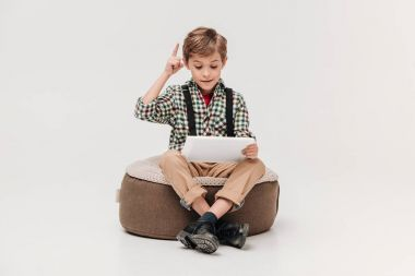 cute little boy using digital tablet and pointing up with finger isolated on grey