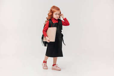 little schoolgirl in black dress with big book isolated on grey