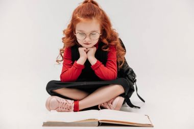 adorable little schoolgirl reading book on floor isolated on grey