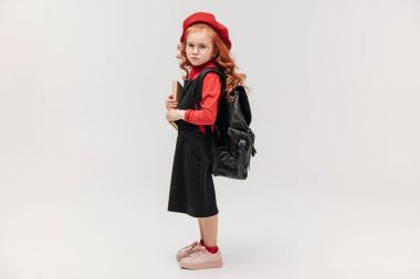 side view of beautiful little schoolgirl in red beret with book and backpack isolated on grey