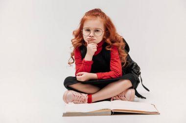 bored little schoolgirl sitting on floor with opened book isolated on grey