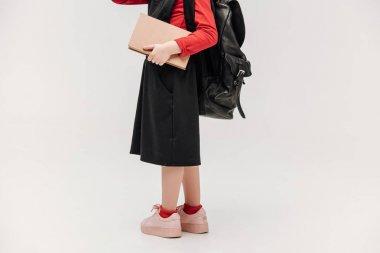 cropped shot of little schoolgirl isolated on grey