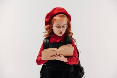 focused little schoolgirl reading book isolated on grey
